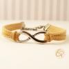 Bracelet en cuir couleur écru avec une breloque représentant l'infini