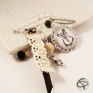 broche argentée dessin de corset dentelle blanche