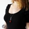 Long sautoir pomme d'amour rouge portée sur le décolleté d'un haut couleur noir