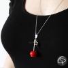 Collier sautoir pomme d'amour rouge porté sur pull noir gros plan bijou pomme d'amour