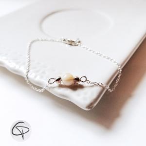 Bracelet féminin orné d'une perle blanche et fine chaîne argentée
