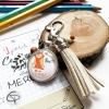 Porte-clé argenté avec dessin sous verre pompon beige breloque feuille