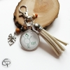 Porte-clé avec pompon en suédine beige et dessin enfantin dans médaillon en verre