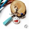Porte-clé métal argenté pompon coton bleu médaillon avec dessin enfantin