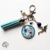 Accessoire pour clefs comprenant un médaillon en verre avec dessin et pompon bleu