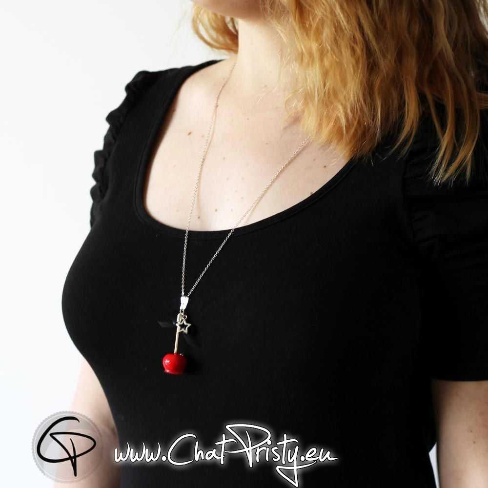 sautoir pomme d'amour rouge porté sur pull foncé moulant