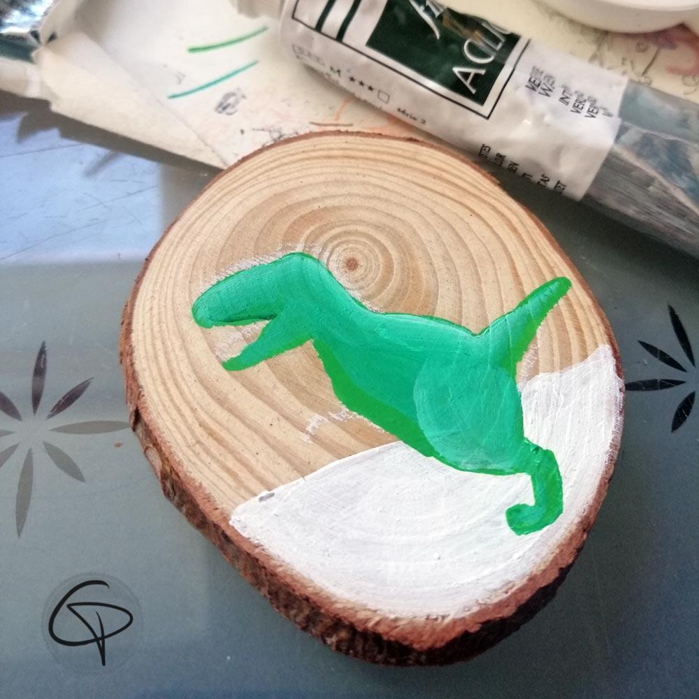 Dinosaure peint sur rondin de bois à mettre dans le sapin